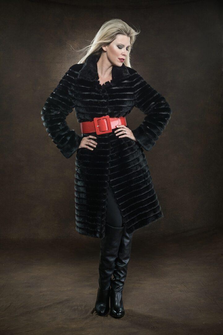 blonde woman wearing black clothing and red belt posing