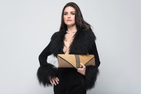 woman in black holding brown clutch bag