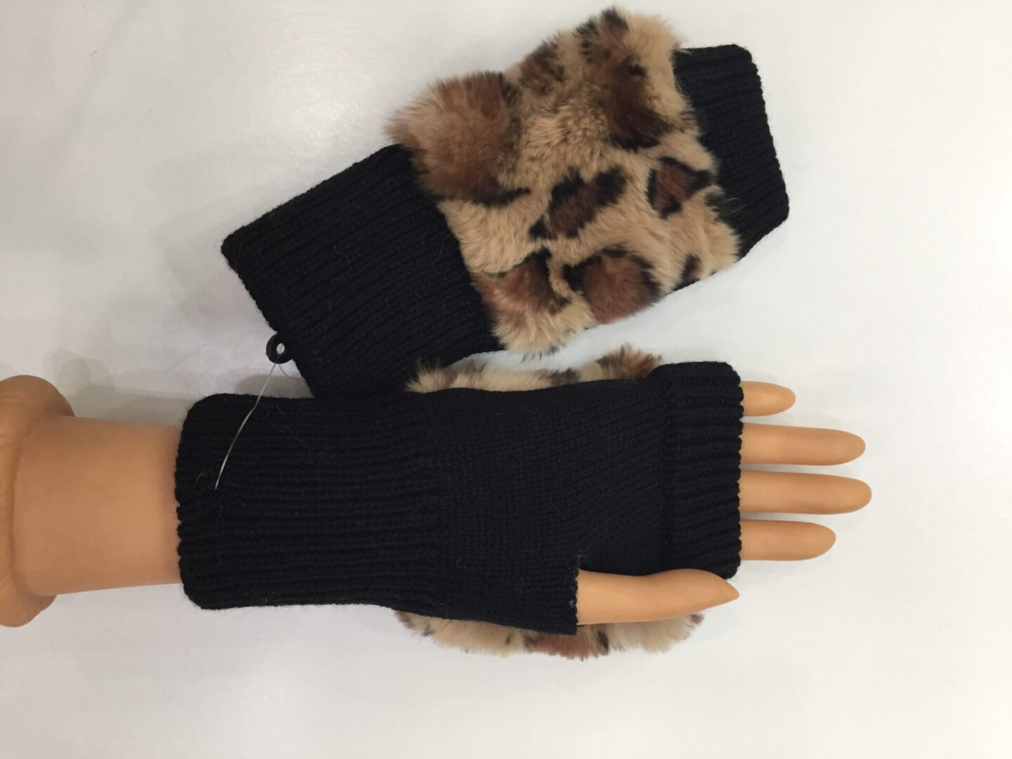 small photo of plastic hand wearing black knit fingerless gloves with animal print