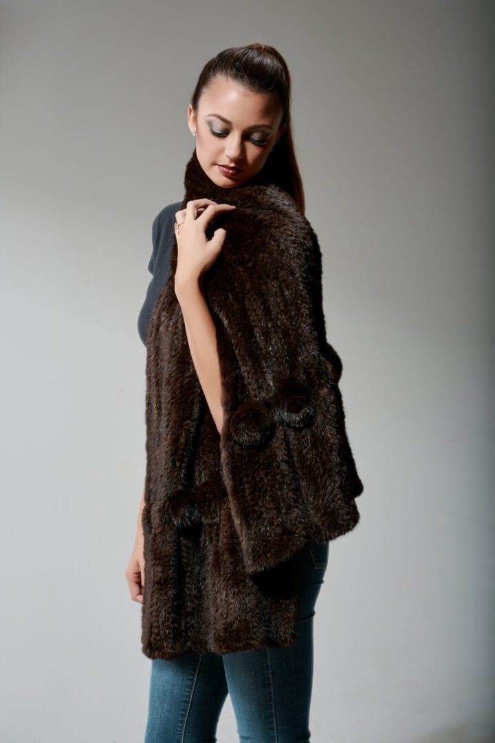 woman with makeup and ponytail modeling knit fur coat